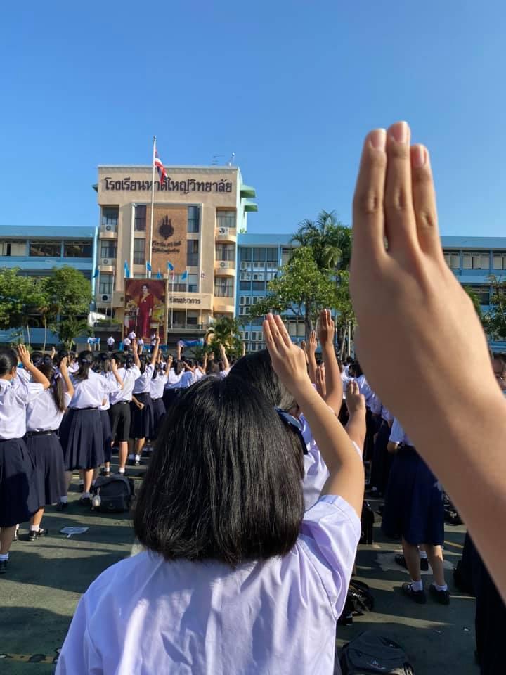 ภาพชูสามนิ้วของกลุ่มนักเรียนมัธยม