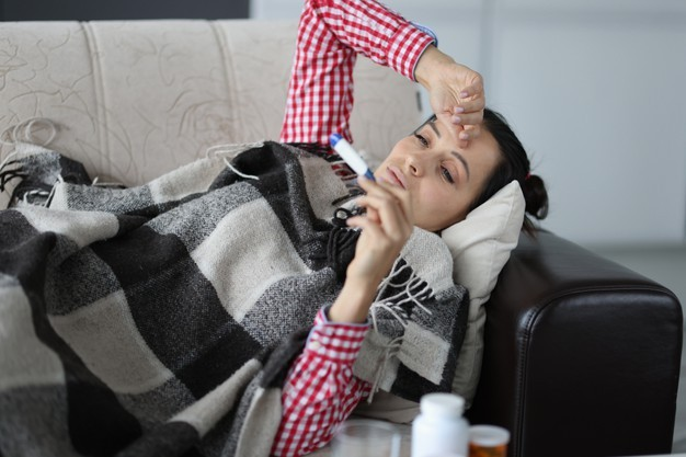 Woman With Cold Lying Sofa Covers Looking Thermometer Isolation Respiratory 151013 20139